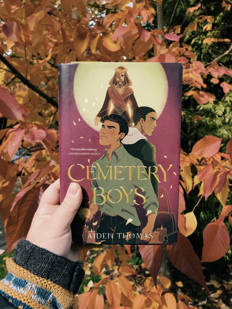 A white hand in a blue and yellow jumper sleeve holds a book in front of a tree with red leaves. The cover of the book has two brown boys with black hair stood back to back, the boy in front is wearing a green shirt tucked into black jeans. The boy in the black is wearing a black jacket over a white hoodie. There is a full moon over their heads and in the reflection of the moon is a skeleton in a red robe with a headdress of roses.