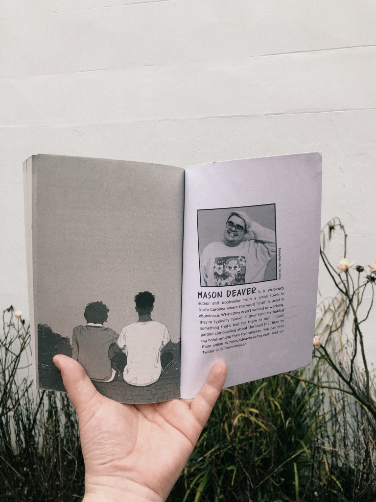 A white hand holds a book open in front of a white wall and white rose bush. On the left page is a black and white illustration of two people sat on a roof, on the right page is a photograph of a white person smiling with rectangle framed glasses and short light hair. The text underneath reads: MASON DEAVER is a nonbinary author and bookseller from a small town in North Carolina where the word y'all is used in abundance. When they aren't weriting or working, they're typically found in their kitchen baking something that's bad for them or out in their garden complaining about the toad that likes to dig holes around their hydrangeas. You can find them online at masondeaverwrites.com and on twitter at @masondeaver.