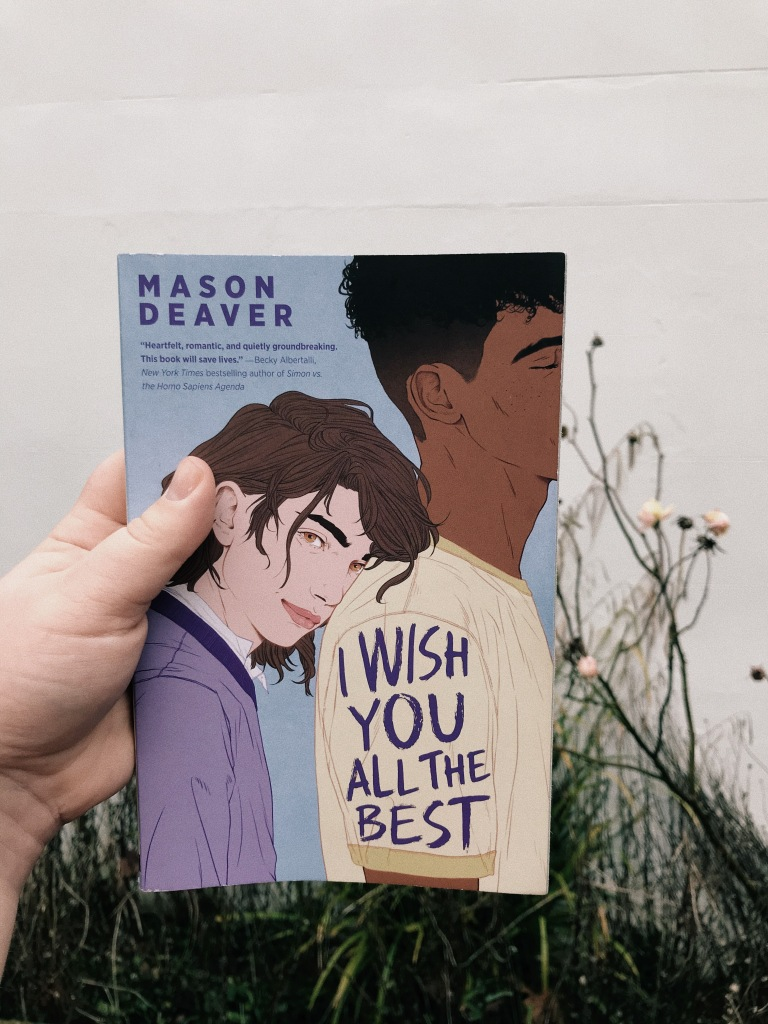 A white hand holds a book in front of a white wall and white rose bush. The background of the cover is blue, and features a white person with long brunet hair wearing a purple sweatshirt over a white shirt. They are leaning on the back of a black boy with short curly black hair, wearing a yellow t-shirt. The text reads: I WISH YOU ALL THE BEST, MASON DEAVER.