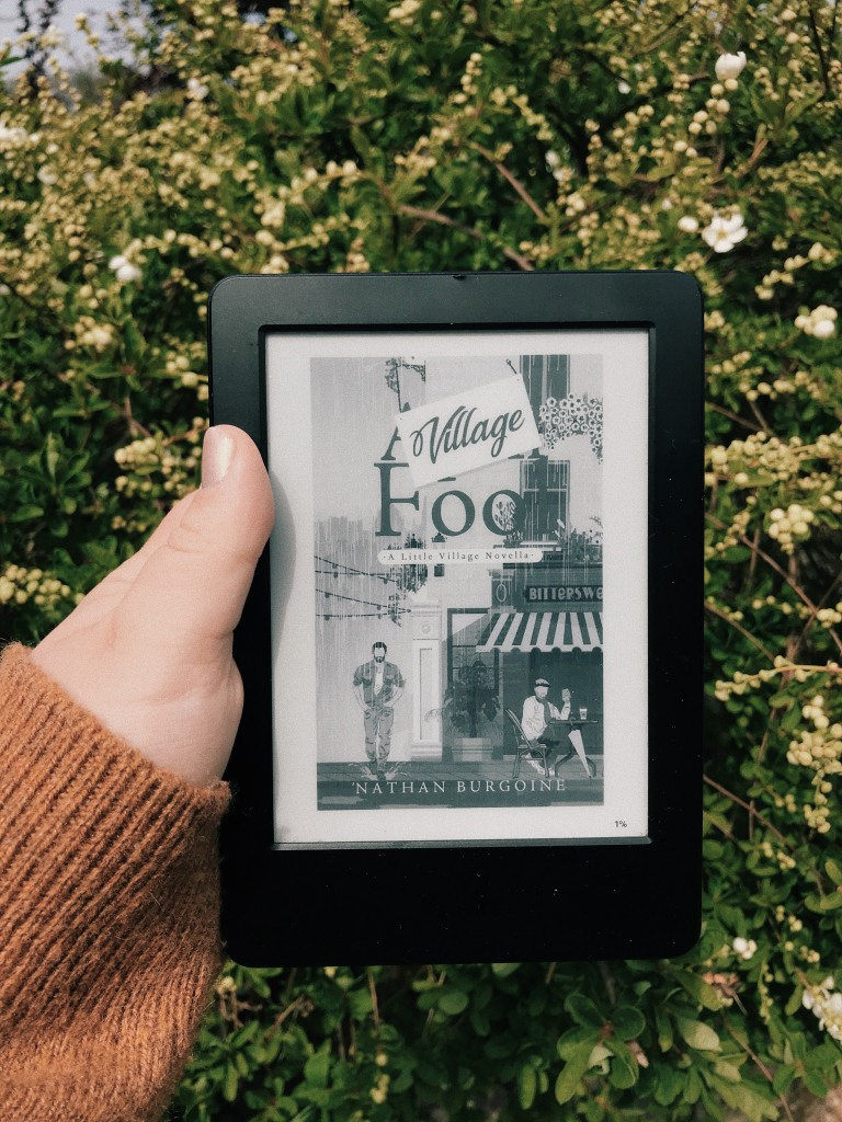 A white hand in a yellow cardigan sleeve holds a kindle in front of a green bush with white flowers on it. There is a book cover on the kindle screen and it reads: Village Fool, A Little Village Novella by Nathan Burgoine. The cover shows a street corner with one man stood out in the rain and another sat drinking coffee under cover.