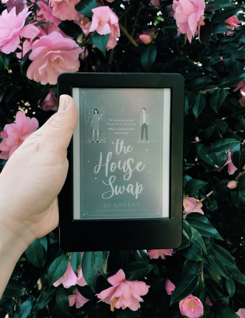 A white hand holds a kindle in front of a pink rose bush. The book cover on the screen is of a woman and man stood in seperate doorways and reads The House Swap by Jo Lovett.